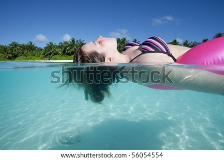 Young woman in a bikini relaxing upon a floating tire within the indian ocean