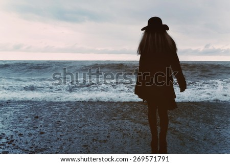 young woman in a black coat on the beach - stock photo