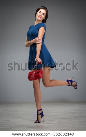 young woman in a blue short dress with handbag
