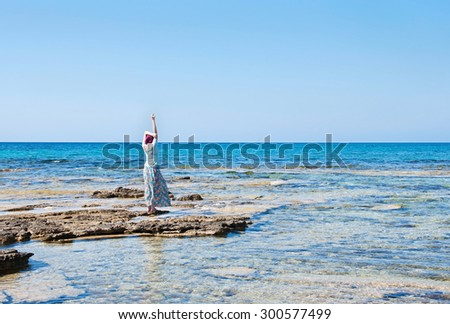 Young woman in a blue summer dress standing on the beach and looking out to sea. - stock photo