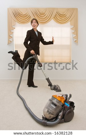Young woman in a business suit vacuuming in an exaggerated pose. Selective focus on the vacuum.