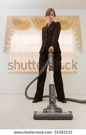 Young woman in a business suit vacuuming in an exaggerated pose. Selective focus on vacuum.