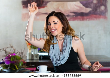 Young woman in a cafe or restaurant, she beckons to someone, perhaps she would like to pay the Bill - stock photo