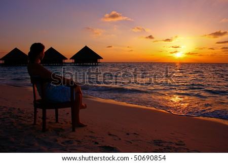 Young woman in a chair at the beach while the sun goes down - stock photo