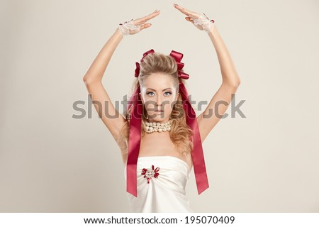 Young woman in a doll style with red bows, holding her hands up. Studio shot. - stock photo