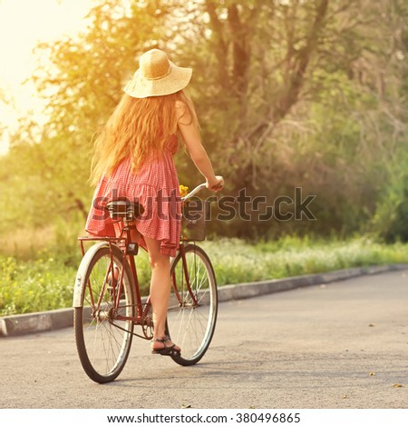 young woman in a dress and hat rides a bike in a summer park. Active people. Outdoors - stock photo
