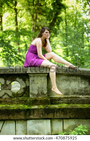 young woman in a dress sitting on stone bridge and looking sad