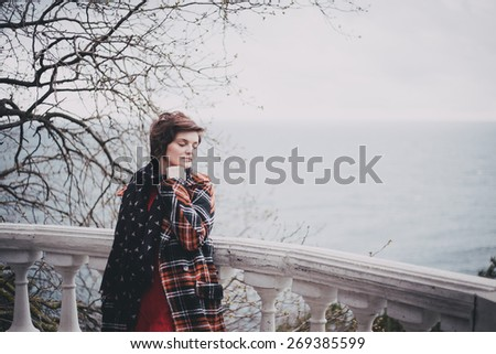 Young woman in a fashion coat standing on a balcony with sea on the background. Sad mood - stock photo