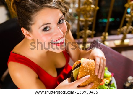 Young woman in a fine dining restaurant eat a hamburger, she behaves improperly