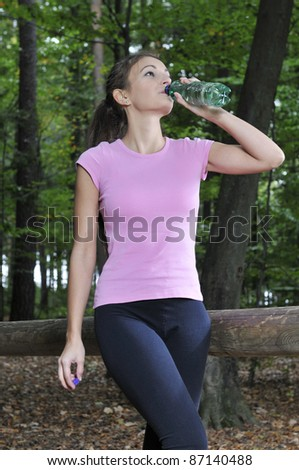 Young woman in a forest is drinking - stock photo