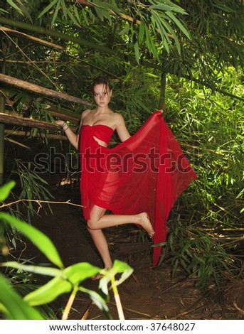 young woman in a forest of bamboo wrapped in cred chiffon - stock photo