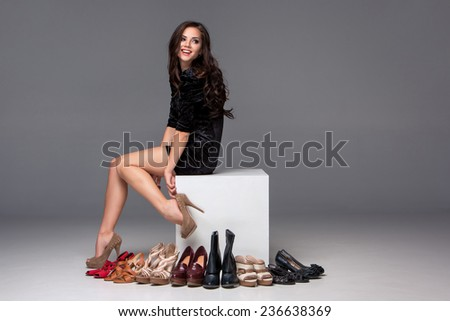Young woman in a gold swimsuit with shopping bags and credit card on a gray background - stock photo