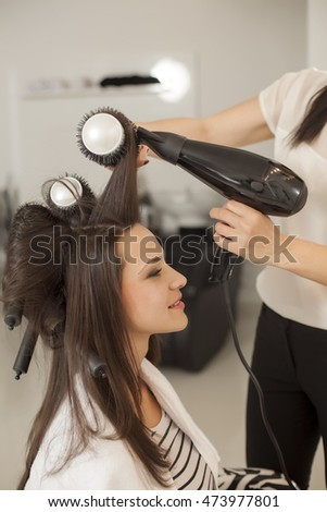 young woman in a hair salon. drying and shaping the hair with a blow dryer and brush
