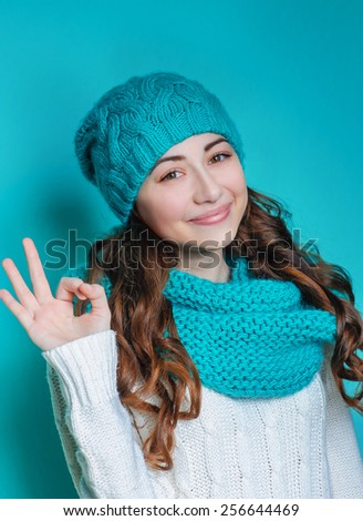 young woman in a knitted hat showing sign okay hands. - stock photo