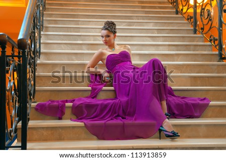 young woman in a long dress lying on the stairs in the hotel lobby - stock photo