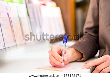 Young woman in a Lotto store playing lottery ticket to win with luck, she fills the ticket with a pen - stock photo