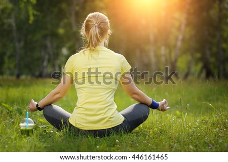 Young woman in a lotus position in a park. Resting after workout. Green detox smoothie.