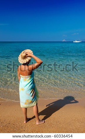 Young woman in a pareo and straw hat, standing on a Mediterranean sandy beach and looking into the blue sea - stock photo