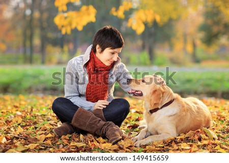 Young woman in a park stroking her retriever dog - stock photo