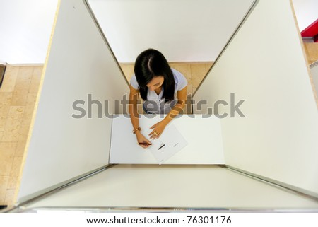Young woman in a polling booth in the electorate casting their vote - stock photo