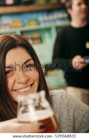 Young woman in a pub with waiter in the background