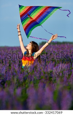 young woman in a rainbow dress and a rainbow kite outdoors - stock photo
