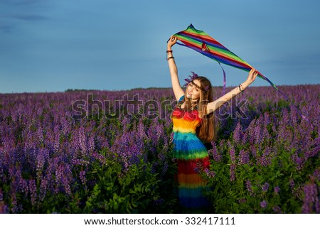 young woman in a rainbow dress and a rainbow kite outdoors