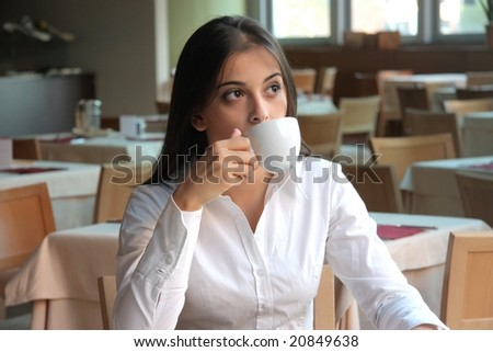 young woman in a restaurant drink cup of tea - stock photo