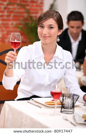 Young woman in a restaurant raising a glass of rose wine - stock photo