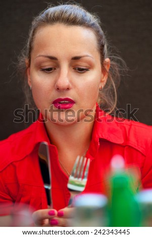 Young woman in a restaurant with cutlery in the hands of - stock photo