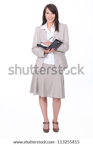 Young woman in a skirt suit writing in a personal organizer - stock photo