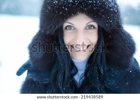 Young woman in a snowy furry hood - stock photo