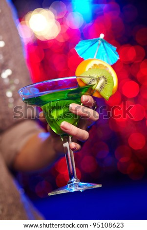 Young woman in a sparkling dress holding a cocktail at a birthday party - stock photo