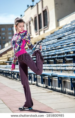 Young Woman in a sports clothing does warm up and stretching on the street the stadium in the afternoon. - stock photo