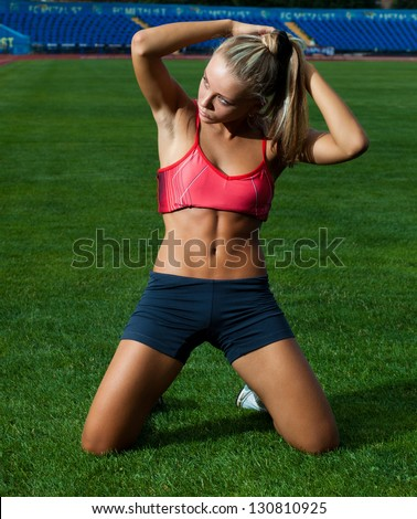 Young woman in a sports suit sitting on her knees on a green football field - stock photo