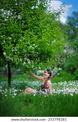 young woman in a spring park sits in flowers. - stock photo
