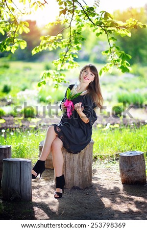 young woman in a spring park with lilies of the valley. - stock photo