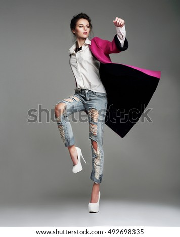 Young woman in a stylish coat posing in the studio. Fashion. Full height.