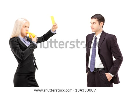 Young woman in a suit showing a yellow card to a young businessman, isolated on white background - stock photo