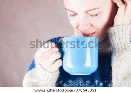 young woman in a sweater with a mug hot or warm of coffee or tea - stock photo