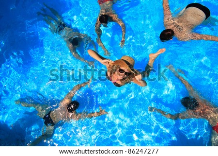 Young woman in a swimming pool surrounded by five man - stock photo