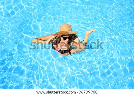 Young woman in a swimming pool with a hat - stock photo