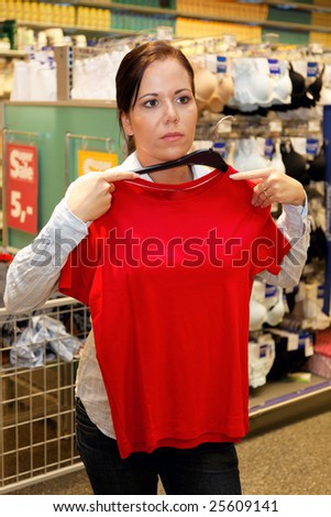 Young woman in a textile market with clothing - stock photo