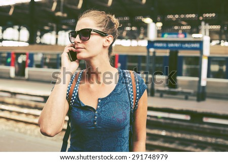 Young woman in a train station, waiting for her train, boarding a train - stock photo