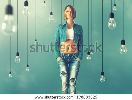 Young woman in a trendy clothes stand between lightbulbs. Unusual art image - stock photo