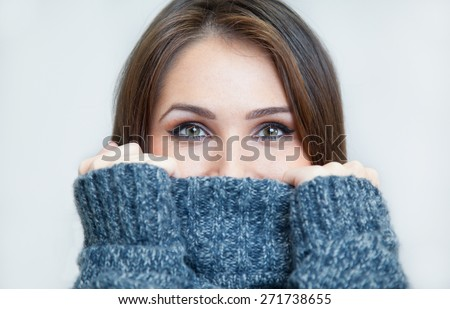 young woman in a turtleneck sweater cold covering her face