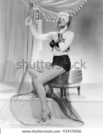 Young woman in a unusual dress, sitting on a stool, looking into a mirror - stock photo