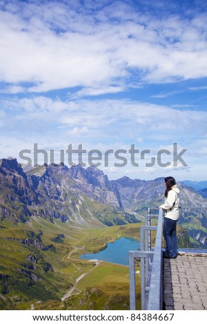 Young woman in a viewpoint of Swiss Alps - stock photo
