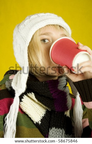 Young woman in a warm sweater, scarf and hat holding a paper cup of coffee. Winter