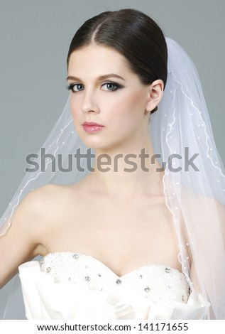 Young woman in a wedding dress. studio portrait on gray background
